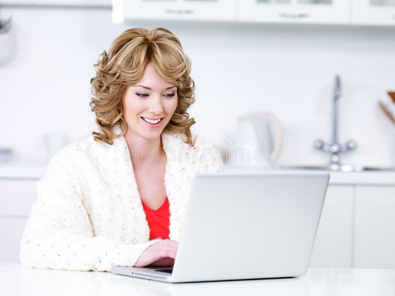 使用妇女的厨房膝上型计算机 免版税图库摄影