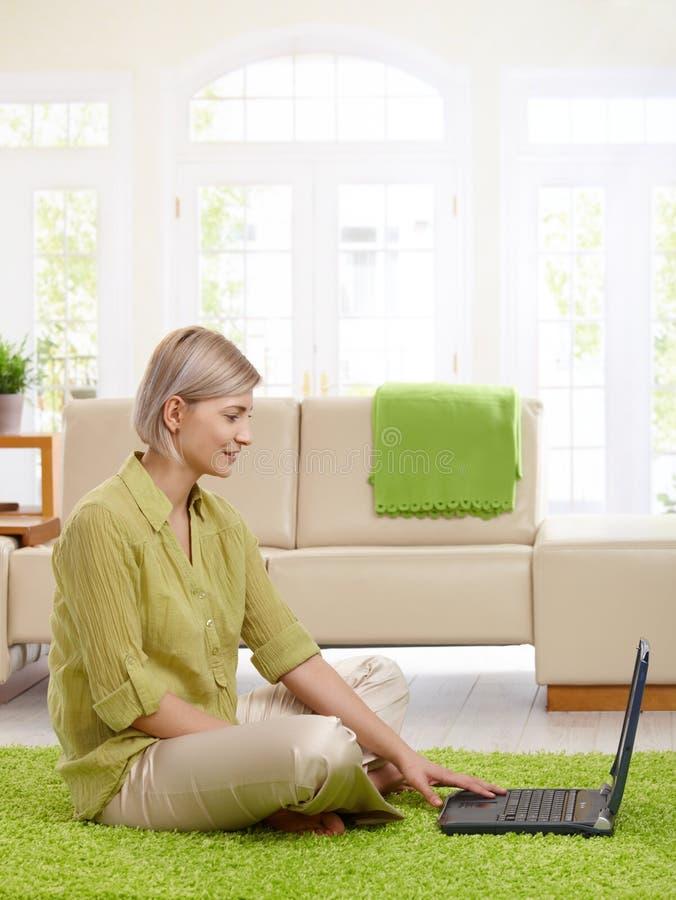使用妇女的家庭膝上型计算机 免版税库存照片