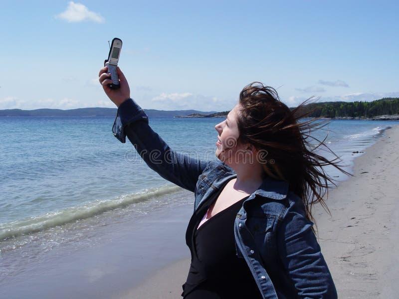 使用妇女的海滩移动电话 免版税库存图片
