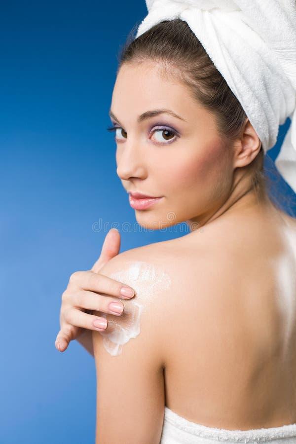 使用妇女的深色的华美的润肤霜温泉 免版税图库摄影