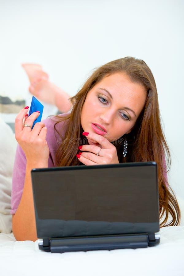 使用妇女的看板卡赊帐净额沉思购物 免版税库存照片