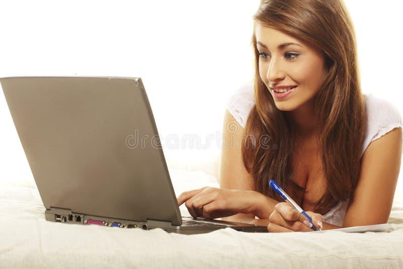 使用妇女的膝上型计算机位于的沙发 库存照片