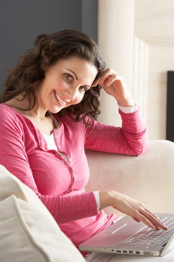 使用妇女的膝上型计算机放松的坐的&# 免版税库存图片