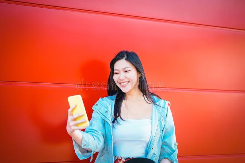使用室外流动的智能手机的愉快的亚洲influncer -观看在新的趋向人脉的中国时尚女孩 免版税图库摄影