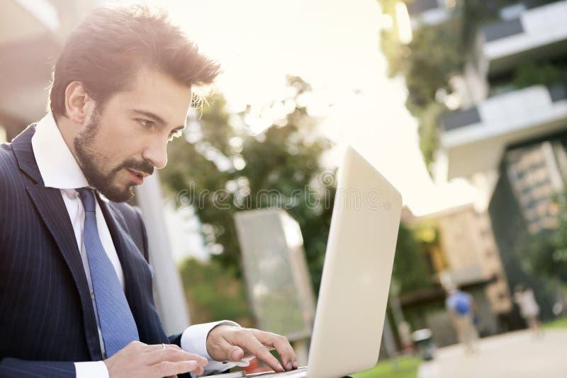 使用室外的膝上型计算机的商人 库存图片