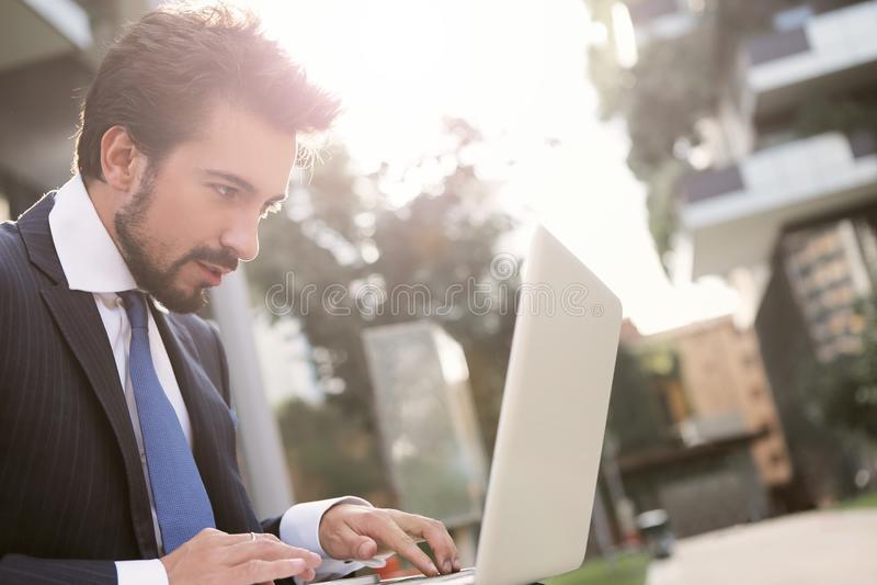 使用室外的膝上型计算机的商人 免版税库存照片