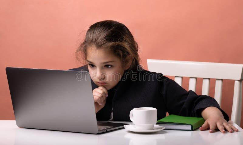 使用对学习的膝上型计算机 工作在办公室的企业女孩 库存图片