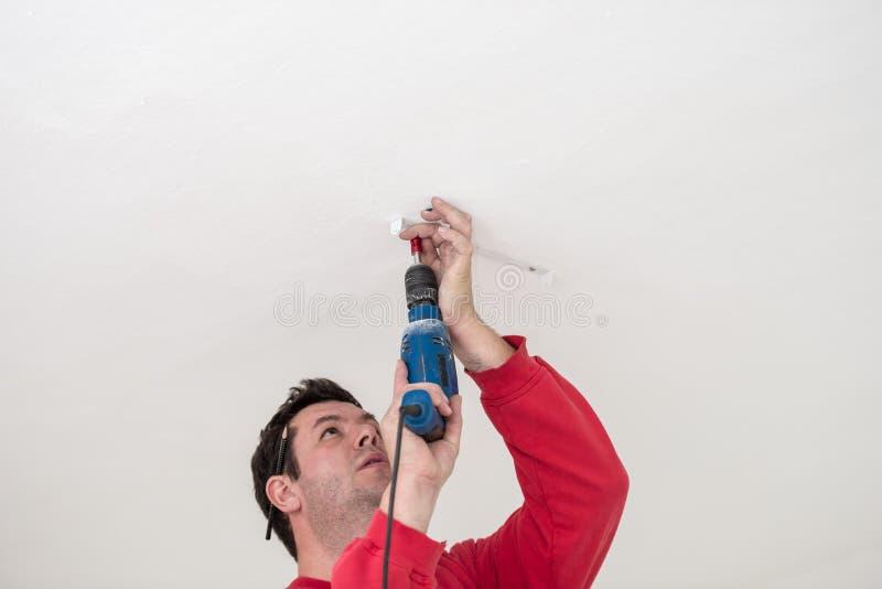 使用小手扶的电钻的建造者 免版税库存图片