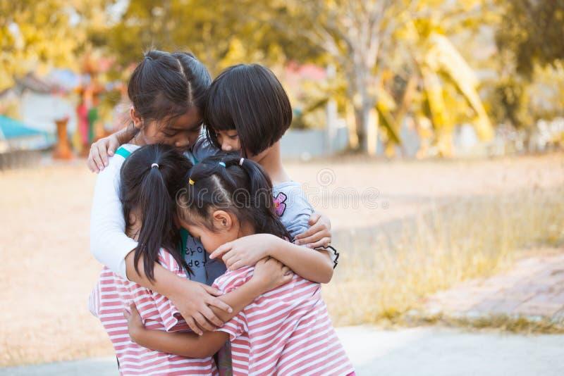 使用小组亚裔的孩子一起拥抱和 库存图片