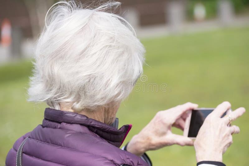使用屏幕流动手机照相机的资深年长人夺取摄影户外 免版税库存图片