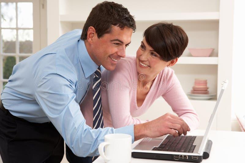 使用工作,夫妇回家膝上型计算机 免版税库存照片