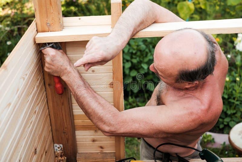 使用工具建筑结构的成熟人外面 免版税库存图片