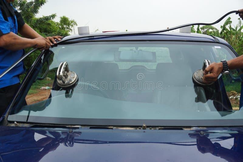 使用工具的玻璃剪裁工修理修理高明的打破的挡风玻璃, wi 库存照片