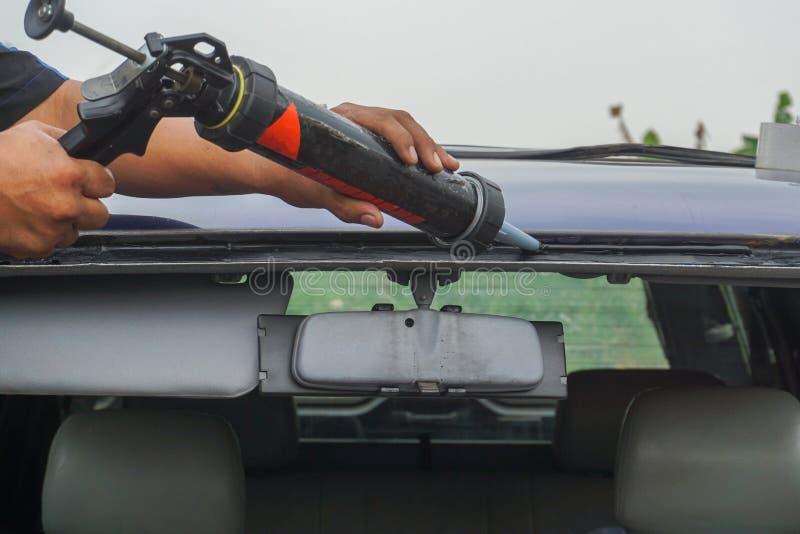 使用工具的玻璃剪裁工修理修理高明的打破的挡风玻璃 库存图片