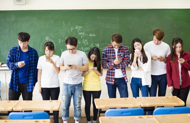 使用巧妙的手机的小组学生在教室 免版税库存图片
