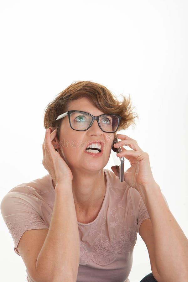 使用巧妙的手机的沮丧的妇女, 免版税库存照片