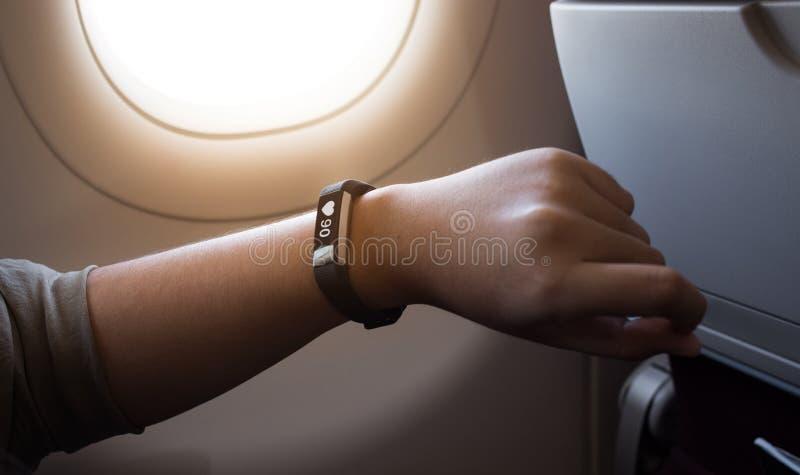 使用巧妙的手表小配件的女性在航空公司 库存照片