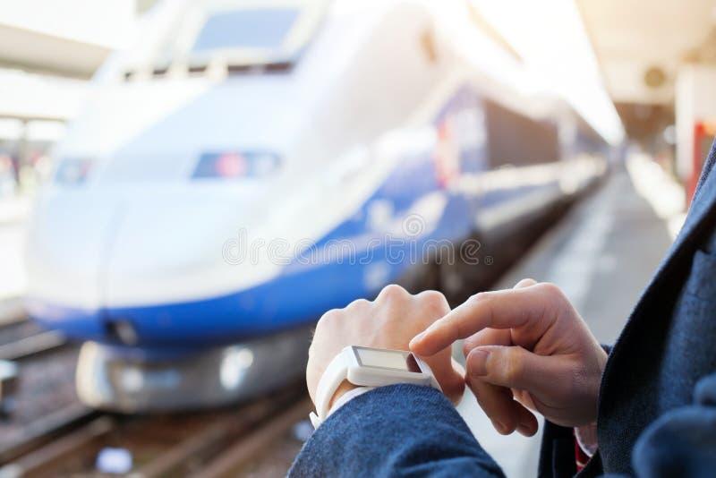 使用巧妙的手表的乘客在火车站 库存图片