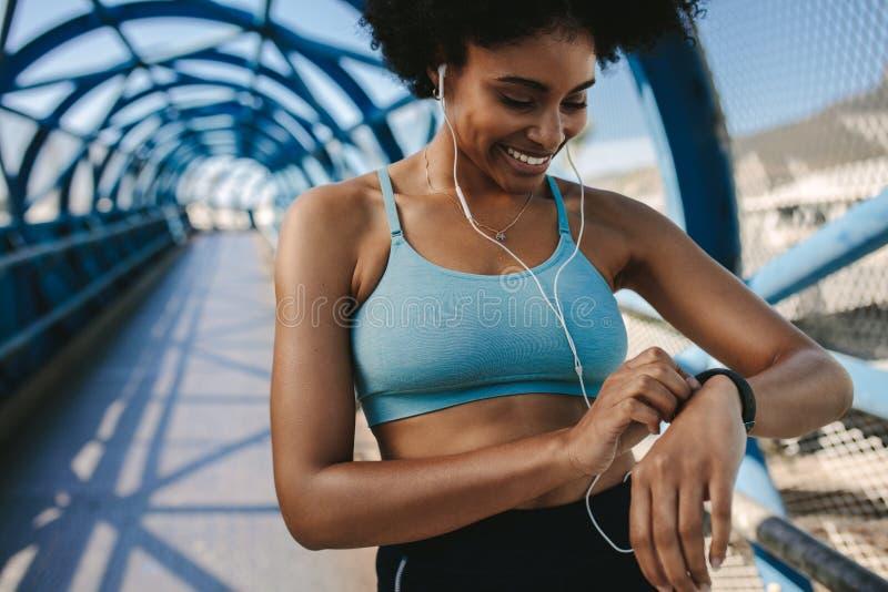 使用巧妙的手表的母赛跑者 免版税库存图片