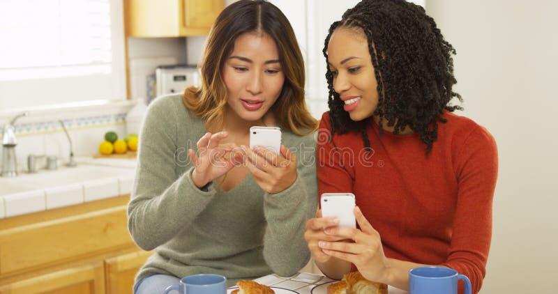 使用巧妙的电话的两个妇女最好的朋友和吃早餐 库存照片