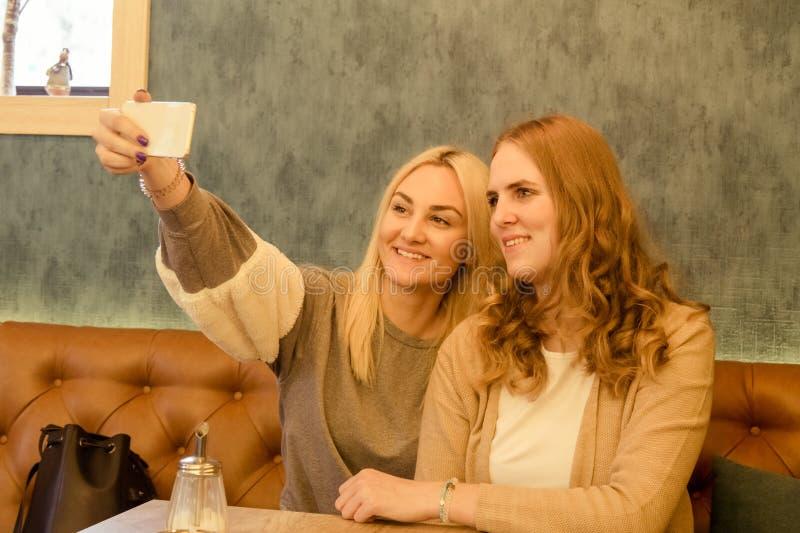 使用巧妙的电话的两个年轻美丽的女孩和做selfie  免版税库存照片