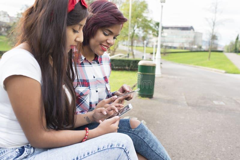 使用巧妙的电话的两个微笑的妇女朋友 免版税图库摄影