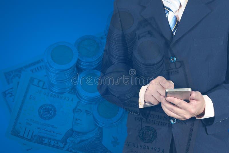 使用巧妙的电话的两次曝光商人在堆硬币 免版税库存照片