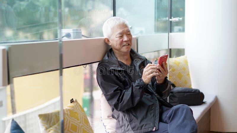 使用巧妙的电话的亚裔老人 通过technolo沟通 库存图片