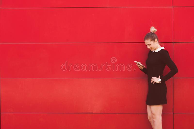 使用巧妙的电话的典雅的女商人画象在前面红色w 免版税库存照片