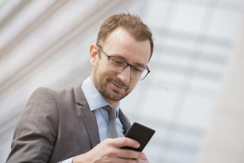 使用巧妙的电话的商人在蓝色玻璃busines前面 库存图片