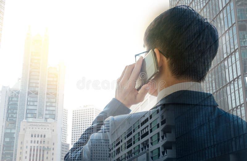 使用巧妙的电话的商人有两次曝光都市风景的和 免版税图库摄影