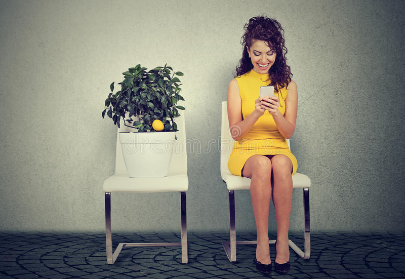 使用巧妙的电话的妇女读电子邮件坐椅子在柠檬树旁边 免版税库存照片
