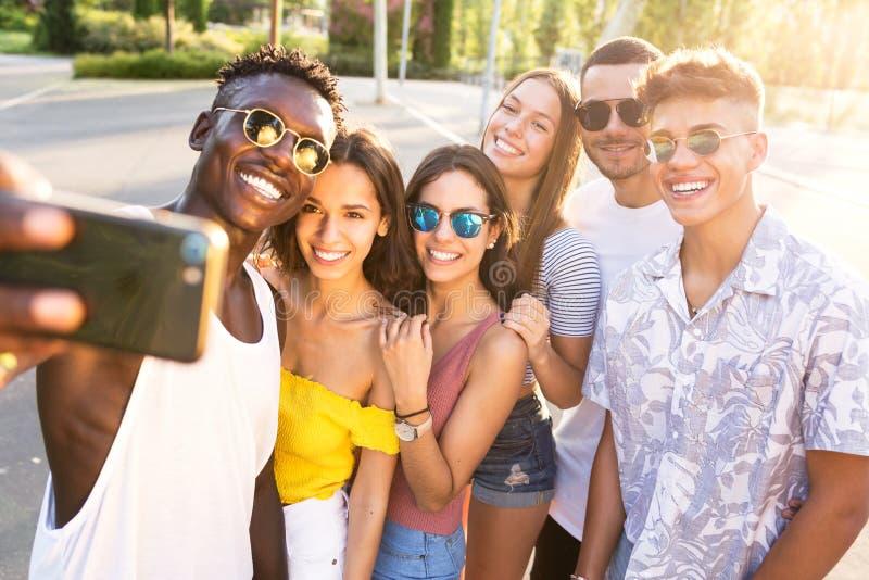 使用巧妙的电话的小组年轻行家朋友在市区 库存照片