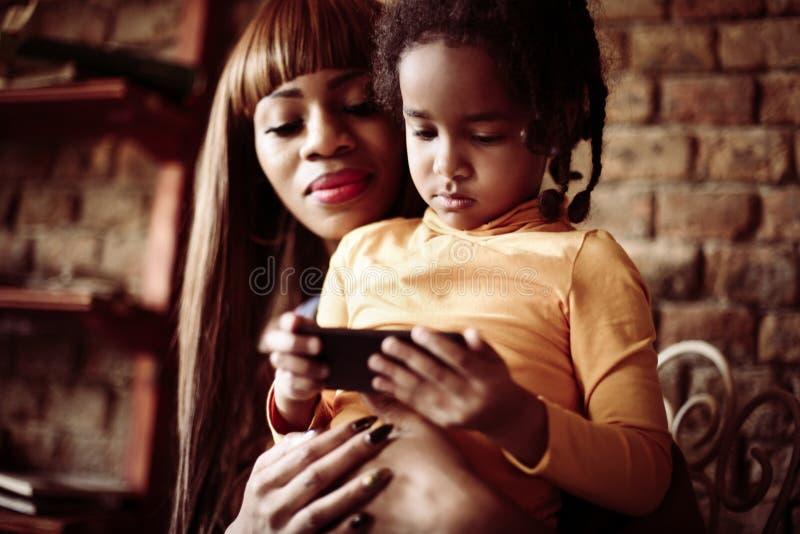 使用巧妙的电话的小非洲女孩 免版税图库摄影