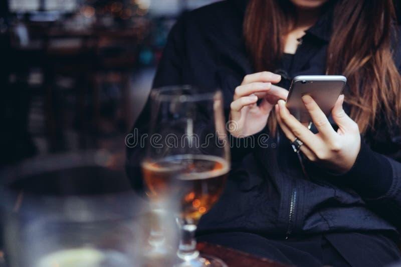 使用巧妙的电话的少妇在酒吧 免版税库存图片