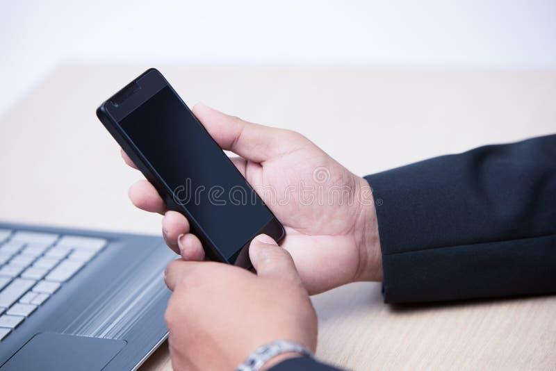 使用巧妙的电话的年轻商人 免版税库存照片