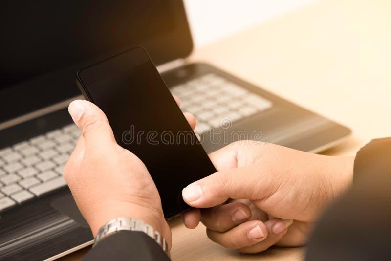 使用巧妙的电话的年轻商人 库存图片