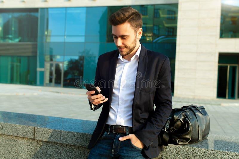 使用巧妙的电话的年轻都市专业人 拿着流动智能手机的商人使用app短信的sms消息佩带的夹克 库存照片
