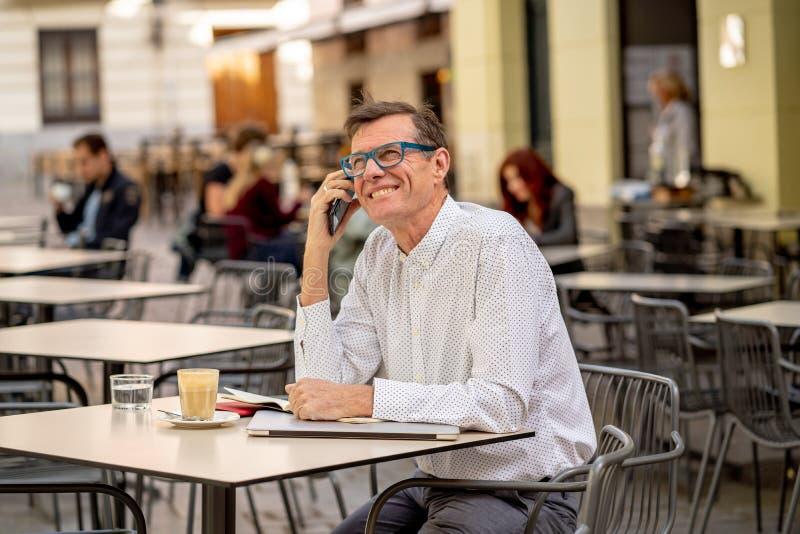 使用巧妙的电话的微笑的可爱的时髦的成熟人检查网上坐在咖啡店之外 库存图片