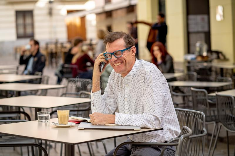 使用巧妙的电话的微笑的可爱的时髦的成熟人检查网上坐在咖啡店之外 免版税库存照片