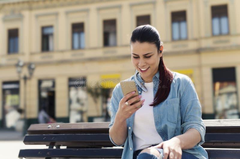 使用巧妙的电话的微笑的妇女 库存图片