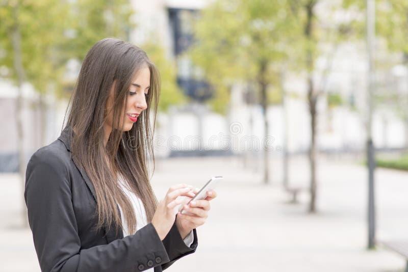 使用巧妙的电话的微笑的成功的女商人在街道 图库摄影