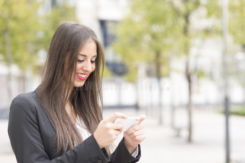 使用巧妙的电话的微笑的成功的女商人在街道 免版税库存图片