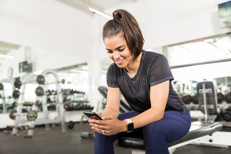 使用巧妙的电话的微笑的适合的妇女在健身俱乐部 图库摄影