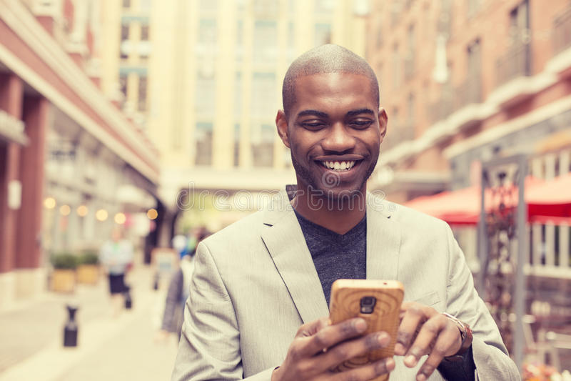 使用巧妙的电话的愉快的微笑的都市专业人 免版税库存图片
