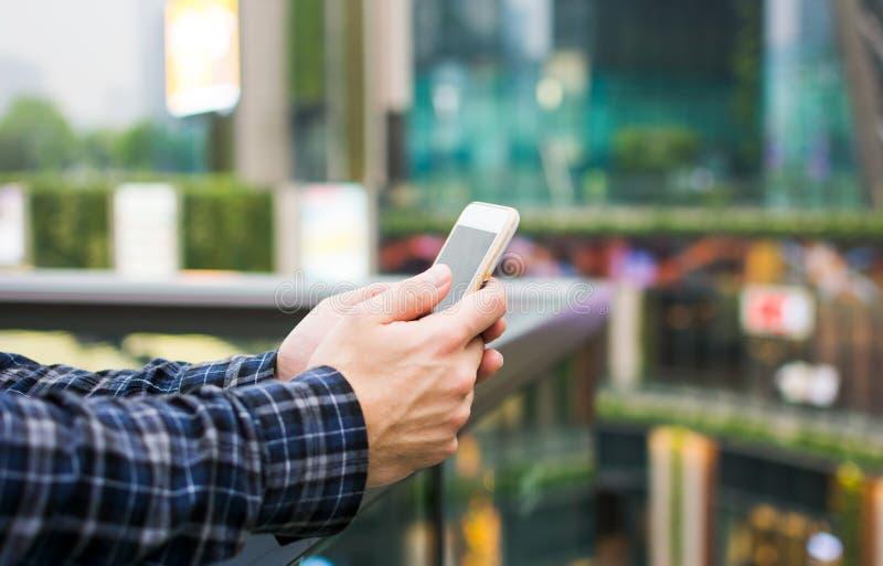 使用巧妙的电话的手在现代商业环境里 图库摄影