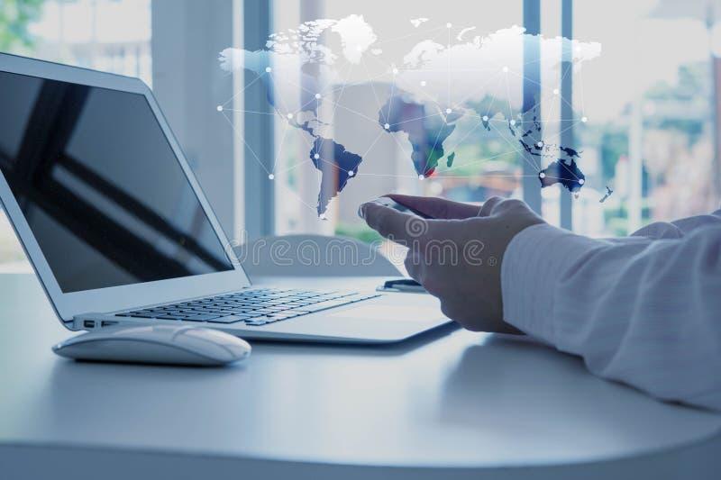 使用巧妙的电话的手有膝上型计算机的,全球化概念 免版税库存图片