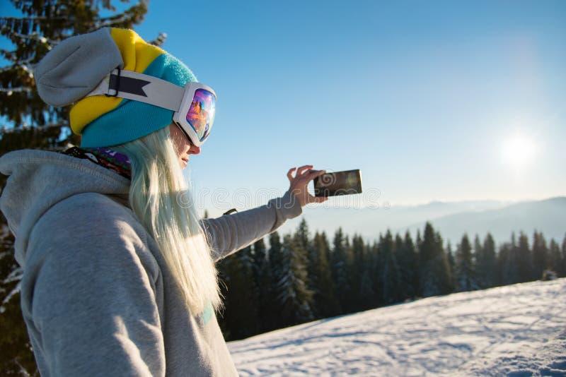 使用巧妙的电话的挡雪板在山 库存图片