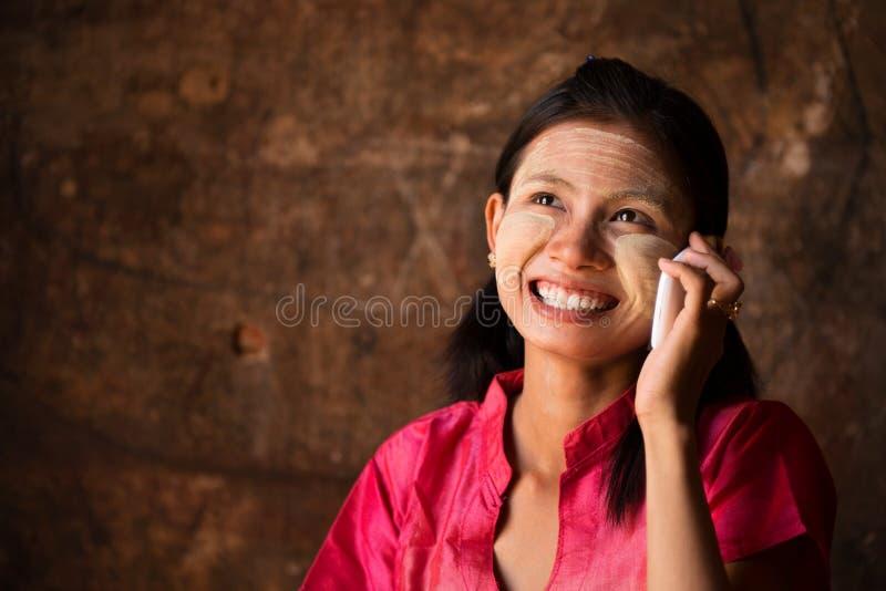 使用巧妙的电话的缅甸女孩。 库存图片