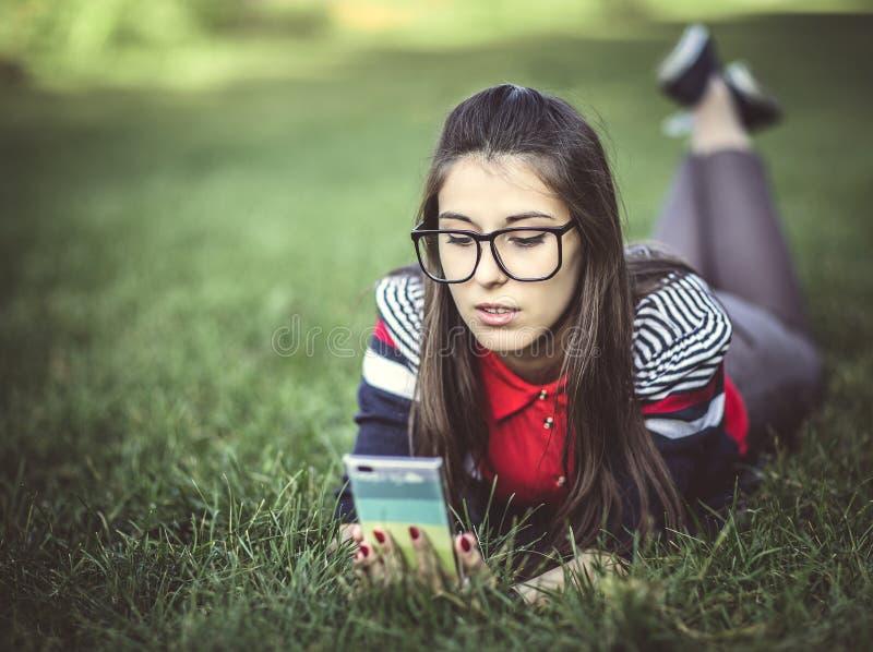 使用巧妙的电话的美丽的年轻行家女孩 图库摄影